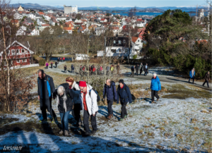 People climbing hill in winter in Stavanger, Norway